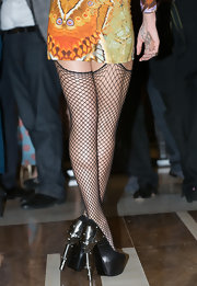 Alice rocked a bold-printed mini with thigh-high fishnet tights and edgy platform pumps with silver hardware heels.