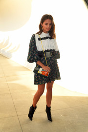 Alicia Vikander looked girly in a Louis Vuitton floral dress with a contrast bib during the brand's Cruise 2020 show.
