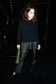 Tallulah Harlech chose a black sweater with a peplum waist and matching pants for the Louis Vuitton fashion show.