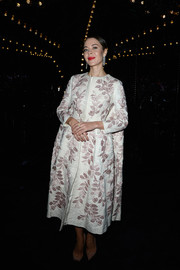 Ulyana Sergeenko went for vintage glamour in a floral-embroidered evening coat when she attended the Louis Vuitton fashion show.