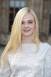 Elle Fanning styled her long locks in sleek layers with a side part for the Louis Vuitton fashion show.