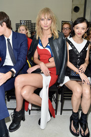 Karlie Kloss sat front row at the Louis Vuitton fashion show wearing black combat boots and colorful cutout dress.