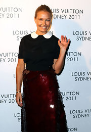 Lara Bingle waved to the cameras in a sweet peter pan collared sweater.