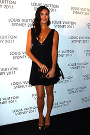 Megan Gale added festive shine to her sultry LBD with a black sequined clutch.