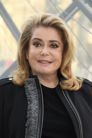 Catherine Deneuve wore her hair down to her shoulders with curled ends at the Louis Vuitton Fall 2019 show.