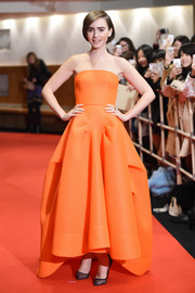 Lily Collins was a brightly clad princess at the 'Love, Rosie' premiere in an orange Maticevksi strapless ball gown featuring a high-low hem and structural detailing on the voluminous skirt.