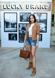 Olivia Culpo matched her jacket with a pair of tan suede ankle boots by Saint Laurent.