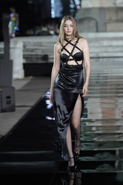 Gigi Hadid was all about bondage glamour in a black Versace dress with a strappy bodice at the LuisaViaRoma CR runway show.