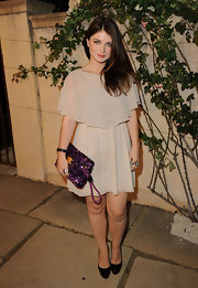 Eve Hewson teamed her flouncy blush chiffon frock with a pair of sturdy black patent pumps at Miu Miu's 'Muta' presentation.