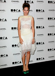 Dasha wears a white sheer cocktail dress. Ruffles and lace and a layer of chiffon complete this delightfully haphazard look. We love the contrasting pumps with a neon accent.