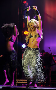 Shakira rocks out on stage in fringed pants and matching leather fringed bracelets.