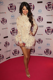 Selena Gomez paired her white frilly frock with gold embellished platform peep-toe pumps.