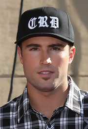 Brody Jenner paired his plaid shirt with a custom made baseball cap.