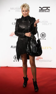Singer Sarah Conner looked very biker-chic at this red carpet soiree, she completed her look with a patent leather hobo bag.
