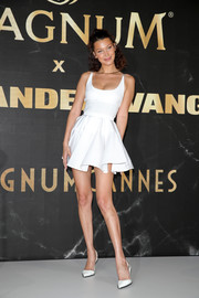 Bella Hadid was cute and flirty in a white skater dress by Alexander Wang at the Magnum photocall during Cannes.
