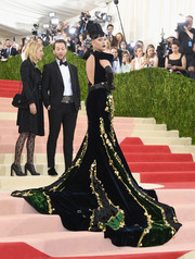 Katy Perry grabbed attention at the Met Gala in a Prada velvet gown, in black, midnight blue, and emerald with gold embroidery and an open back.