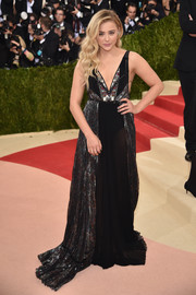 Chloe Grace Moretz looked subtly sexy at the Met Gala in a semi-sheer Coach gown, in black with metallic panels.