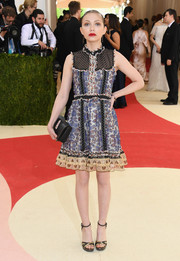 Tavi Gevinson styled her dress with a pair of black and gold platform sandals.
