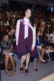 Kate Nash hid her figure under an unflattering purple dress layered over a long-sleeve tie-neck blouse during the Mara Hoffman fashion show.