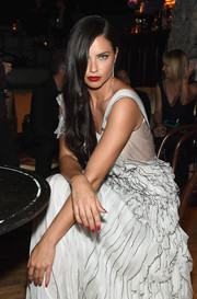 Adriana Lima sported red nail polish and lipstick for a pop of color to her white dress at the Decadence celebration.