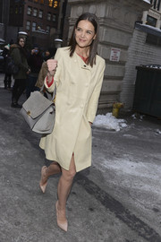 Katie Holmes arrived for the Marchesa fashion show wearing a stylish ivory leather coat over a red dress.