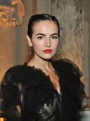 Camilla Belle paired her dramatic black ensemble with intricate drop diamond earrings.