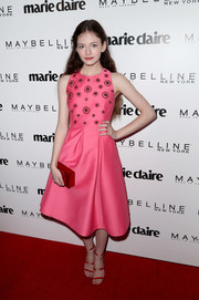 Mackenzie Foy finished off her colorful ensemble with a red box clutch by Edie Parker.