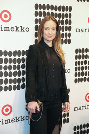 Olivia Wilde accessorized with a gold chain-strap bag for a bright spot to her all-black look when she attended the Marimekko for Target launch.