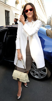 French actress Marion is seen wearing a winter white trench coat and a pair of hot red shades. She kept her outfit classy with a white quilted shoulder bag.