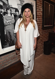 Kesha attended the 'Bowie Unseen' exhibition looking exotic in a white asymmetrical-hem tunic and matching pants.