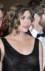 Elizabeth wore an art deco beaded head band with her sleek dress for the Cannes Film Festival.