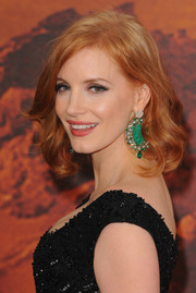 Huge emerald chandelier earrings by Piaget added major glamour to Jessica Chastain's look.