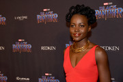 Lupita Nyong'o glitzed up her red outfit with a layered gold necklace by Douriean.