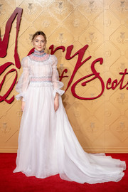 Saoirse Ronan looked divine at the European premiere of 'Mary Queen of Scots' in a white Carolina Herrera gown with Juliet sleeves and a colorful smocked neckline and waist.