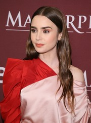 Lily Collins wore her hair in barely-there waves at the Masterpiece photocall.