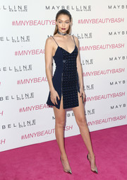 Gigi Hadid highlighted her fabulous legs in an embellished navy mini dress with spaghetti straps and double slits during the Maybelline New York Beauty Bash.