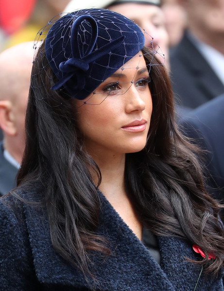 Meghan Markle polished off her look with a navy velvet fascinator by Philip Treacy.