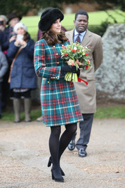 Kate Middleton looked appropriately festive in a teal and red plaid coat by Miu Miu while attending Christmas Day church service.