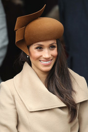 Meghan Markle accessorized with a sculptural brown hat by Philip Treacy for Christmas Day church service.