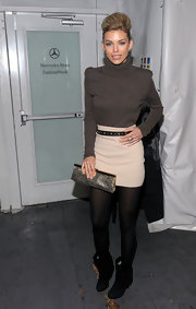 AnnaLynne bundled up in a bold shouldered gray turtleneck.