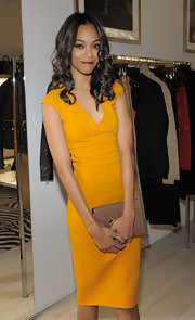 Zoe Saldana accented her bright marigold sheath with a cocoa Quinn snakeskin envelope clutch.
