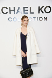 Sistine Stallone layered a white wool coat over a navy dress for the Michael Kors fashion show.