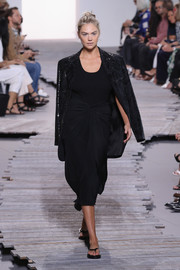 Kate Upton sashayed down the Michael Kors runway wearing a black sarong skirt and a matching top.