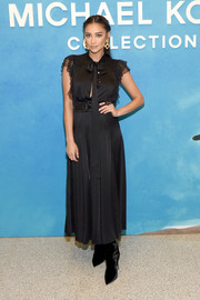 Shay Mitchell was classic and sweet in a tea-length dress with a pussybow and lace detailing at the Michael Kors Spring 2019 show.