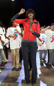 Michelle Obama was a bright sight in a neon-orange zip up jacket during the debut of a school exercise program.