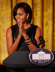 Michelle Obama finished off her ensemble with layers of black and gold bangle bracelets.