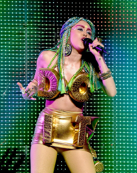 Miley Cyrus matched a pair of gold bangles with her metallic 'DO IT' outfit for her performance at the Wiltern Theatre.