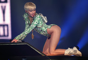 Miley Cyrus teamed dollar sign-embellished cowboy boots with a high-cut bodysuit for a performance in London.