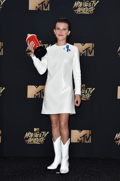 Millie Bobby Brown Cowboy Boots [movie,stranger things,white,clothing,flooring,fashion model,shoulder,fashion,outerwear,carpet,dress,leg,millie bobby brown,tv awards,best actor in a show,room,press room,the shrine auditorium,california,mtv,zac efron,2017 mtv movie tv awards,mtv movie tv awards,emma watson,actor,film,television,celebrity]