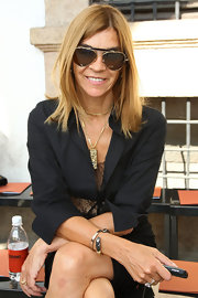 Carine wears her hair straight and in a slight side part.